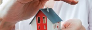 hands presenting a small model of a house